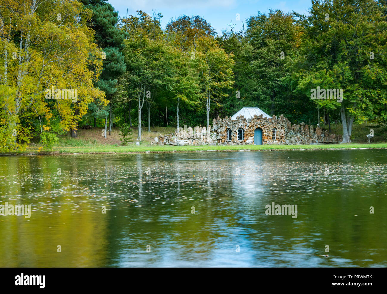 Gosford House Pleasure Grounds and Policies, Longniddry, East Lothian, Scotland, United Kingdom, 4th October 2018. UK Weather: Autumn colours in the mature trees in Gosford House estate are lit by sunshine. The quirky rubble stone built curling lodge by the artificial lake - Stock Image