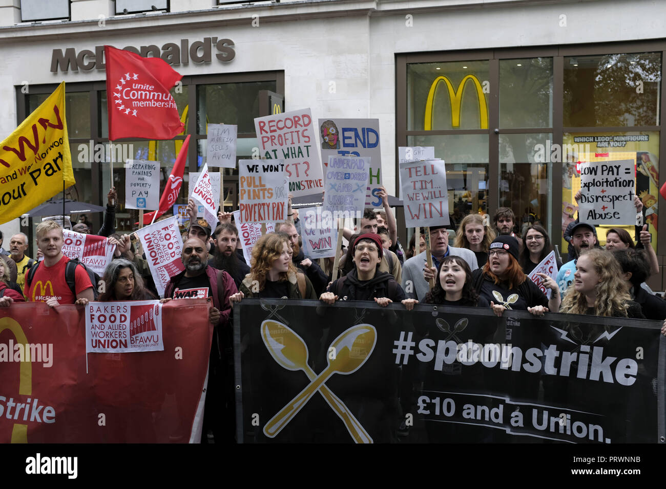 London, Greater London, UK. 5th Oct, 2018. Protesters seen holding banners and flags outside Mc Donalds during the protest.Wetherspoons, TGI Fridays, and McDonald's workers rally together in London to demand better working conditions and a fair pay in the hospitality industry. Credit: Andres Pantoja/SOPA Images/ZUMA Wire/Alamy Live News - Stock Image