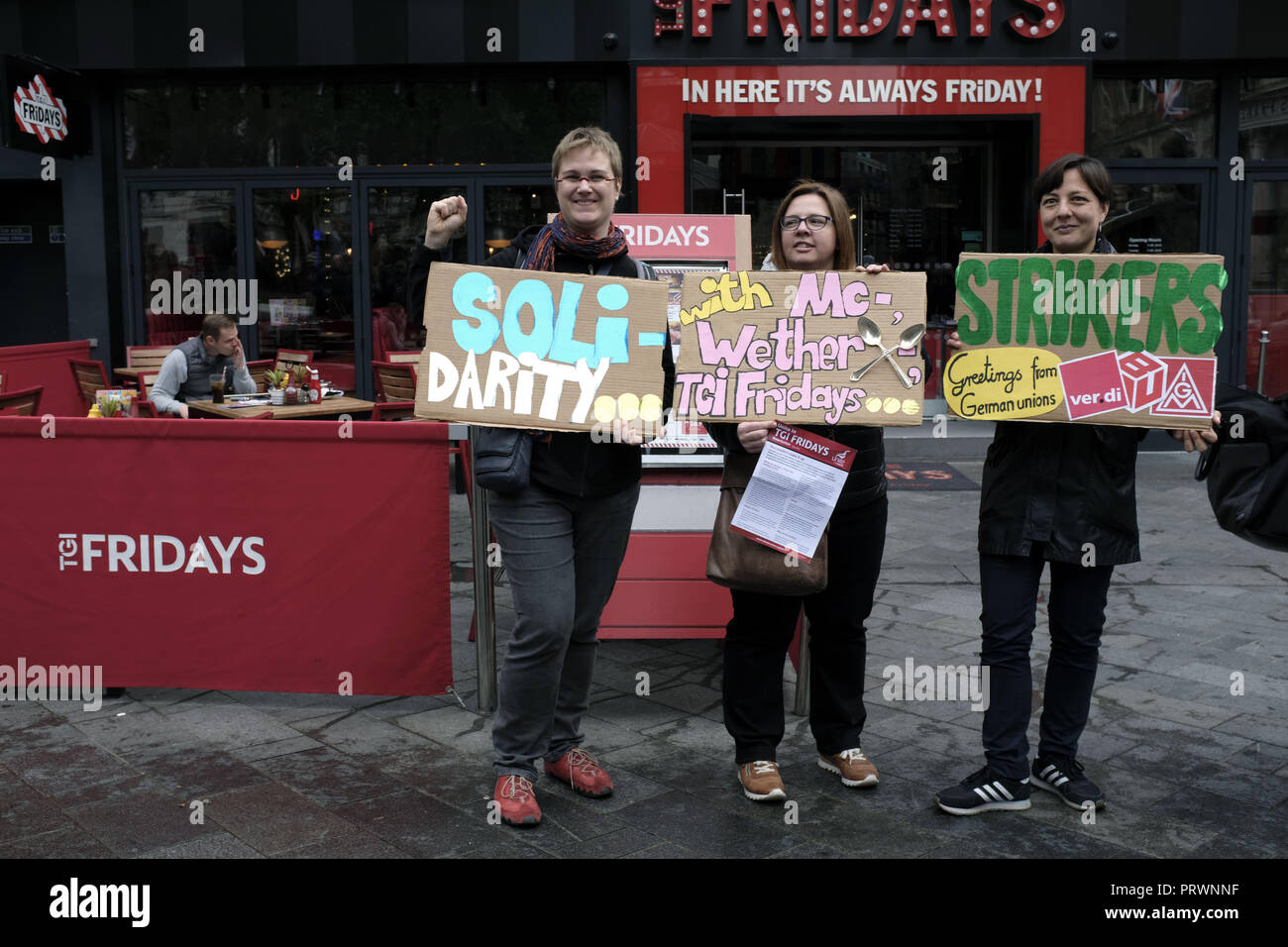 London, Greater London, UK. 5th Oct, 2018. Protesters seen holding posters in front of a TGI Fridays during the protest.Wetherspoons, TGI Fridays, and McDonald's workers rally together in London to demand better working conditions and a fair pay in the hospitality industry. Credit: Andres Pantoja/SOPA Images/ZUMA Wire/Alamy Live News - Stock Image
