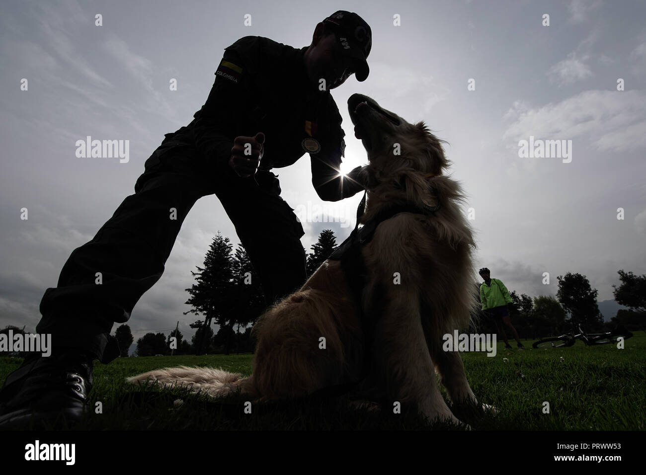 Bogota, Colombia. 4th Oct, 2018. A member of the Colombian Technical Investigation Team (CTI) takes part in a recognition ceremony along with a dog in Bogota, Colombia, on Oct. 4, 2018. A recognition ceremony to highlight and recognize the work of the canines and equines that serve in Bogota was held here to mark the World Animal Day on Thursday. Credit: Jhon Paz/Xinhua/Alamy Live News - Stock Image