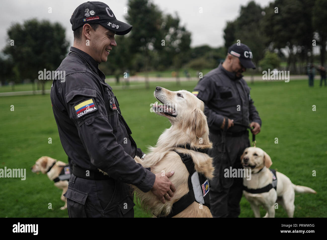 Bogota, Colombia. 4th Oct, 2018. Members of the Colombian Technical Investigation Team (CTI) take part in a recognition ceremony along with their dogs in Bogota, Colombia, on Oct. 4, 2018. A recognition ceremony to highlight and recognize the work of the canines and equines that serve in Bogota was held here to mark the World Animal Day on Thursday. Credit: Jhon Paz/Xinhua/Alamy Live News - Stock Image
