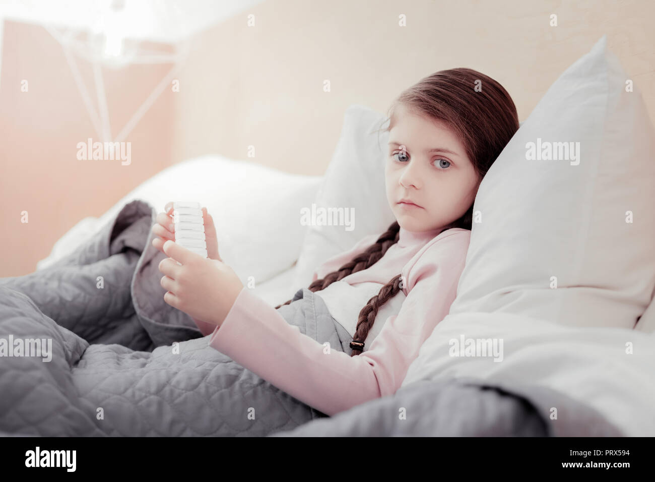 Close up of pale sick girl in bed - Stock Image