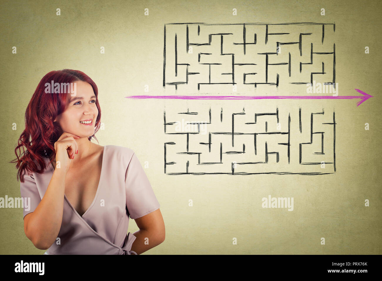 Young redhead pensive woman holding hand under chin thoughtful looking to find a solution to escape from maze. Young businesswoman breaking the rules, - Stock Image