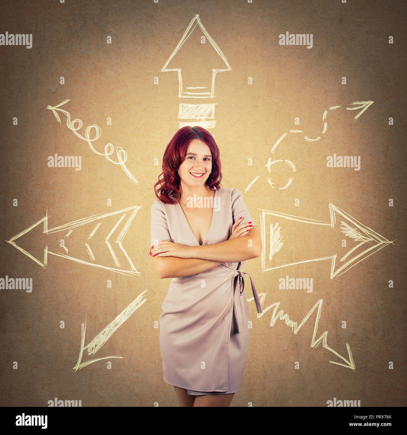 Redhead woman standing with arms crossed and arrows pointed to different directions over colorful background. Difficult choice, decide which way to go - Stock Image