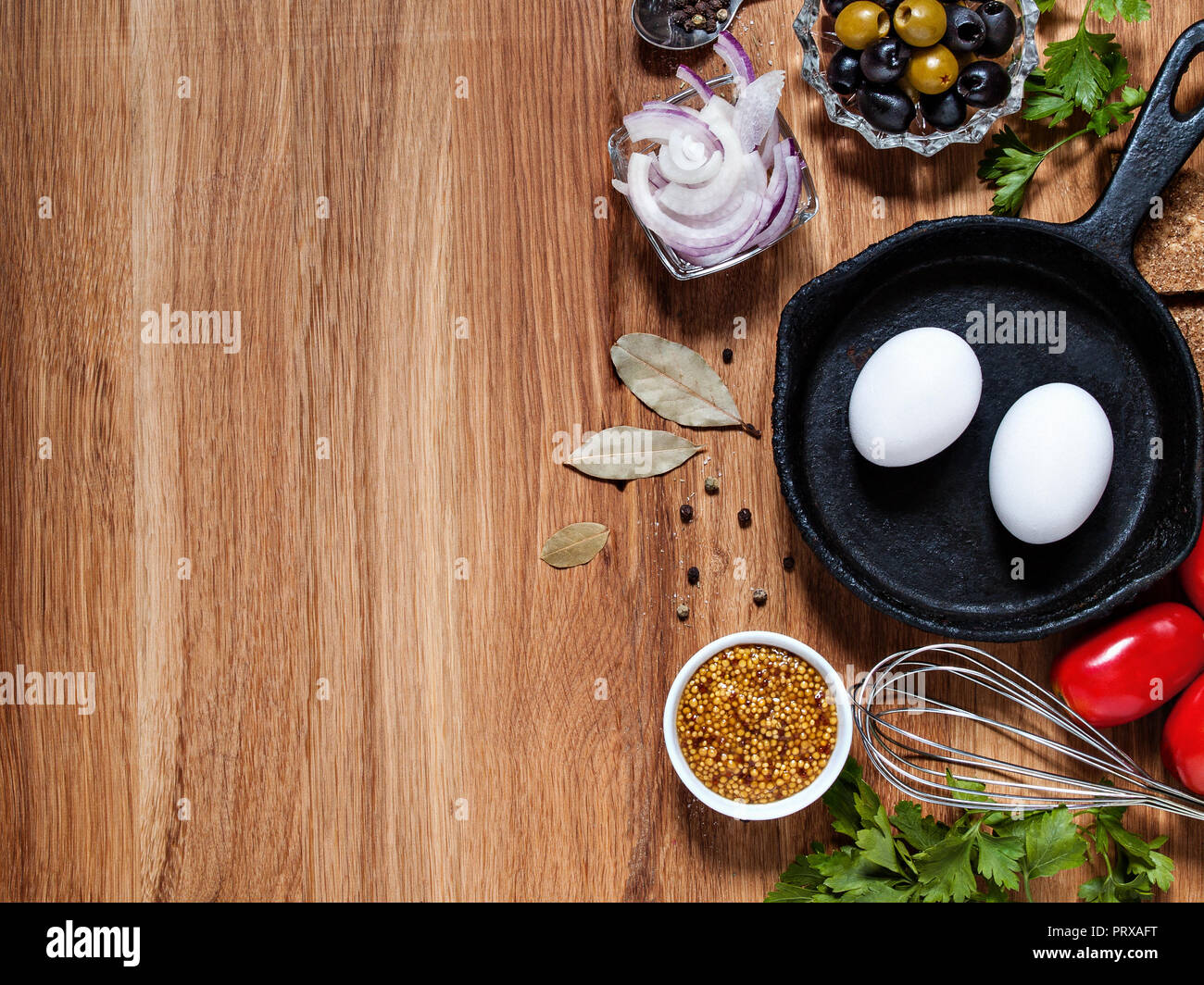 On a wooden background horizontally with copyscera chicken eggs in a cast iron pan, onions, olives, tomatoes, greens, a beater - Stock Image