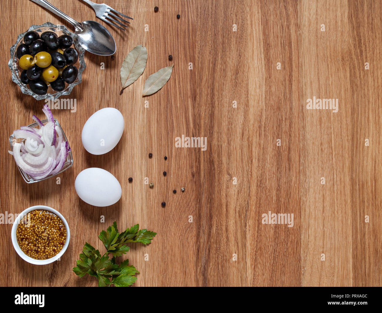 Olives, mustard, chicken eggs, red onion, bay leaf lie on a wooden background horizontally with copy-space - Stock Image