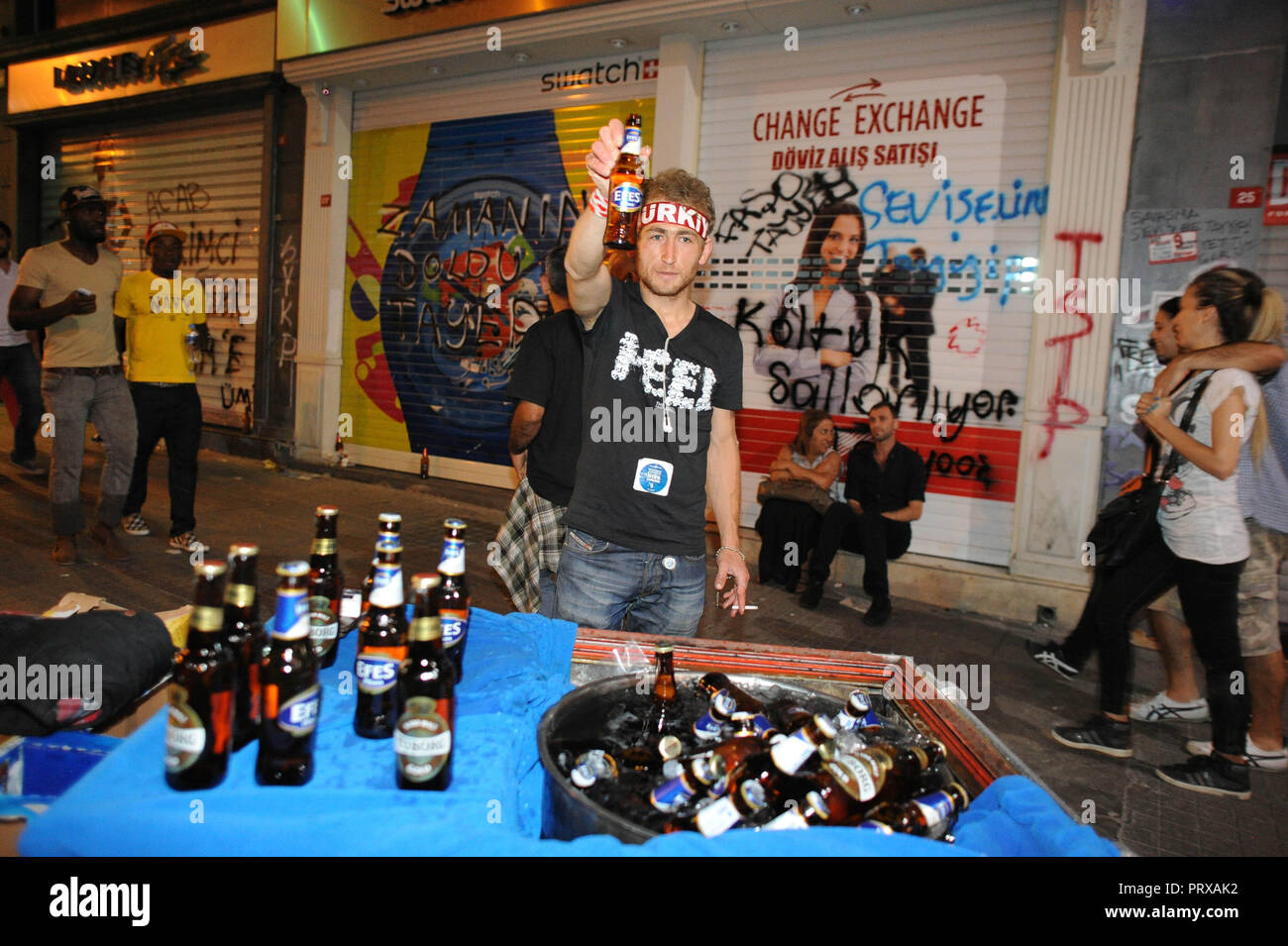 June 7, 2013 - Istanbul, Turkey: A street vendor sell alcohol very late at night near Taksim Square. Several Turkish demonstrators drink beers and celebrate loudly in public space as a way to protest against a new law prohibiting the take-away sale of alcoholic beverages between 10 pm and 6 am. Scene de celebrations dans la rue principale de Taksim, Istiklal, durant l'occupation du parc Gezi *** FRANCE OUT / NO SALES TO FRENCH MEDIA *** - Stock Image
