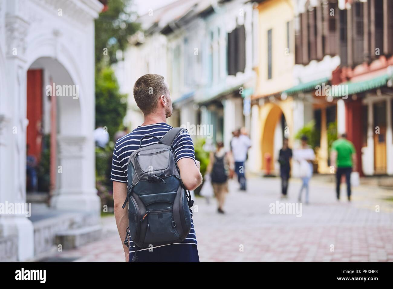 Traveler in city. Young man with backpack admiring architecture of old houses in Singapore. - Stock Image