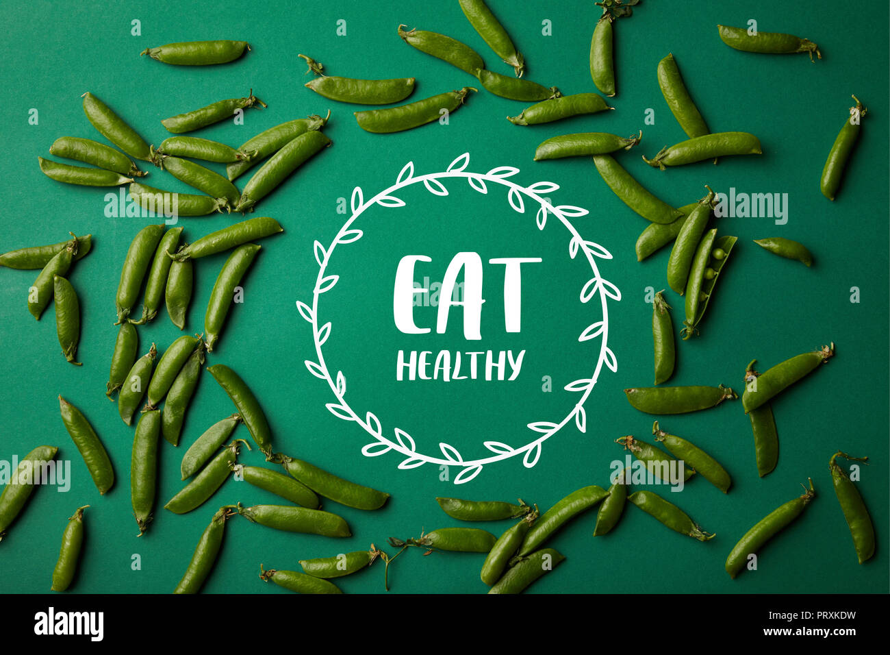 top view of round frame made of pea pods on green surface with 'eat healthy' lettering - Stock Image