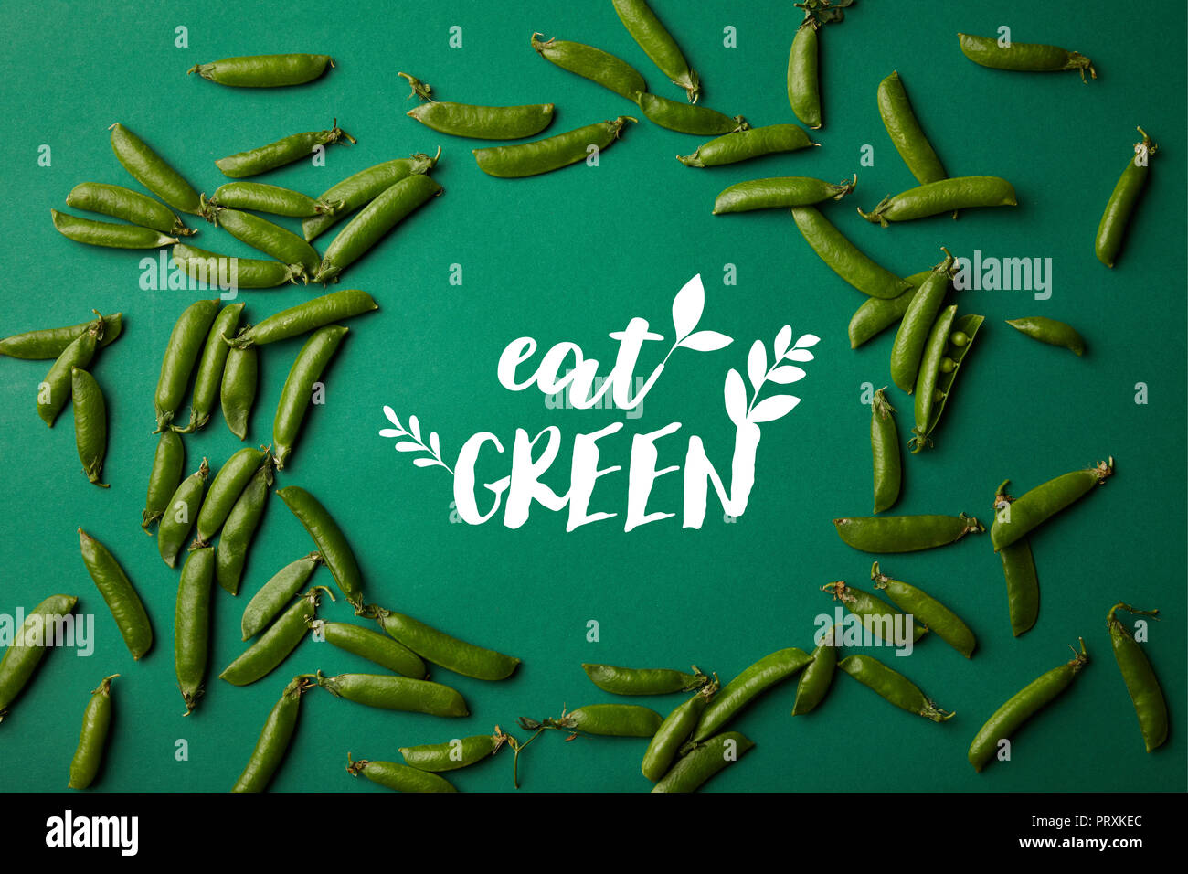 top view of round frame made of pea pods on green surface with 'eat green' lettering - Stock Image