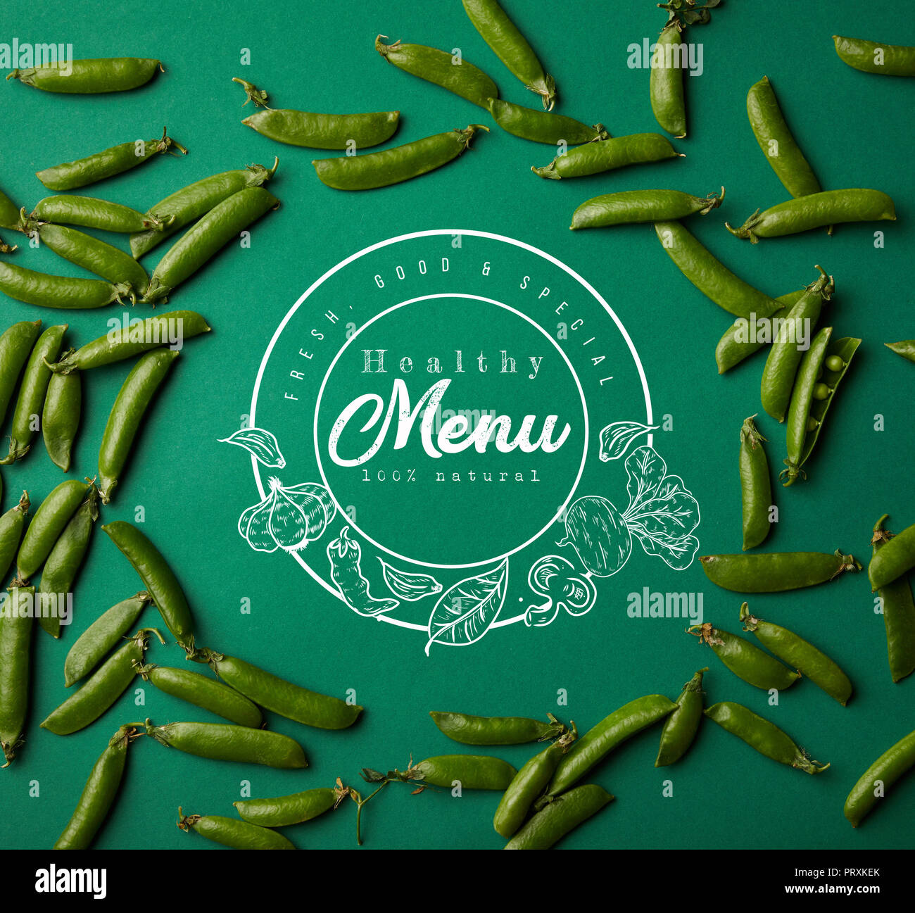 top view of round frame made of pea pods on green surface with 'healthy menu' lettering - Stock Image
