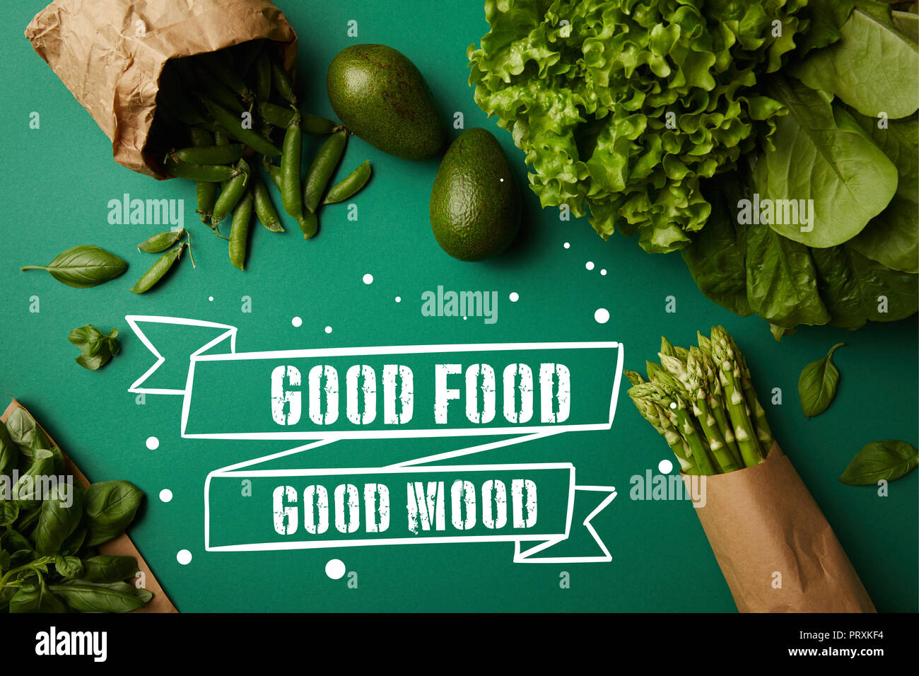top view of different green ripe vegetables on green surface with 'good food - good mood' inspiration - Stock Image