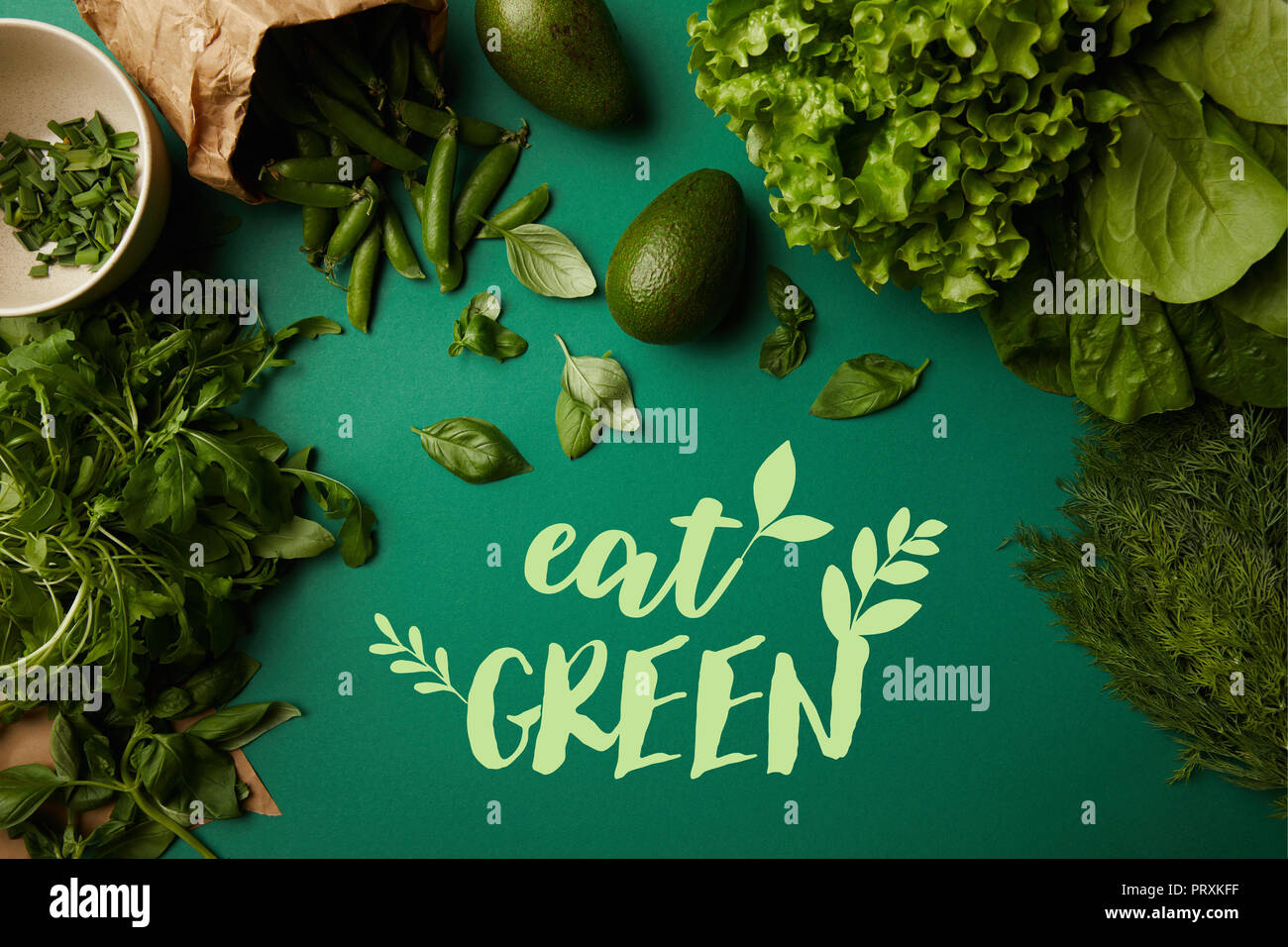 top view of different ripe vegetables on green surface with 'eat green' lettering - Stock Image