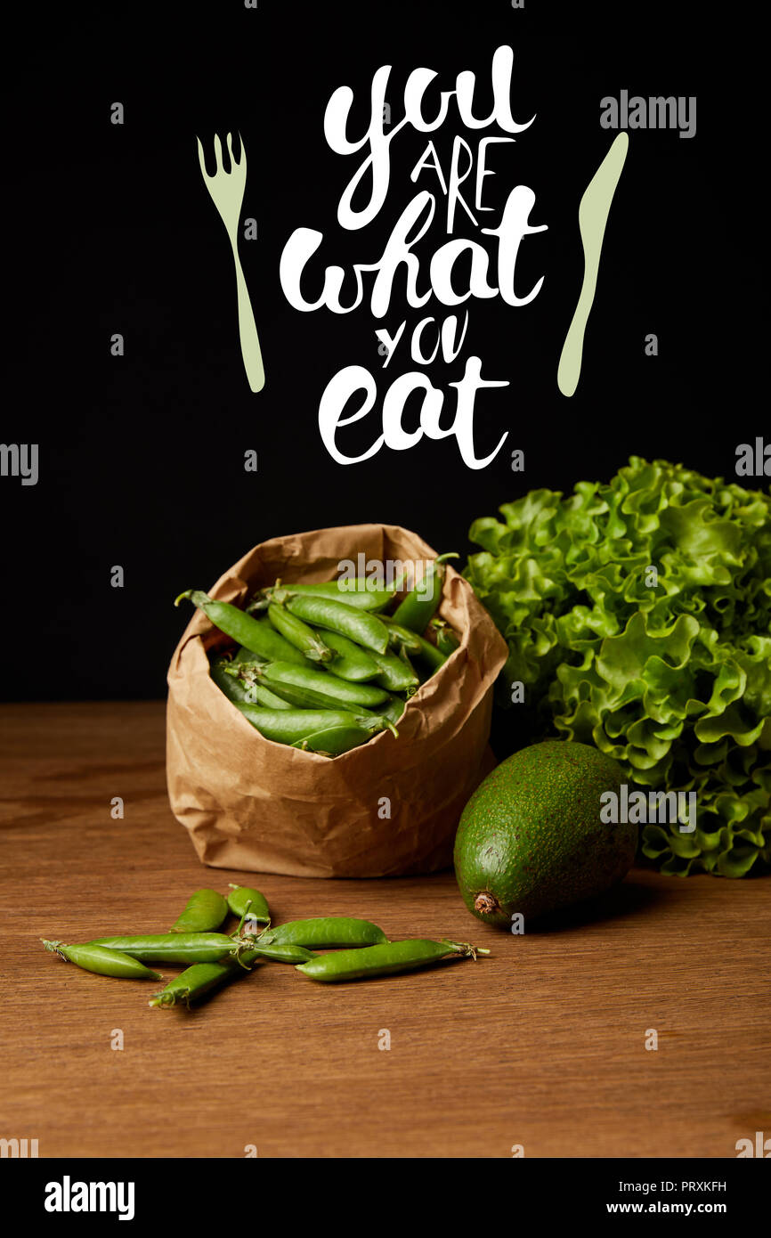close-up shot of avocado, green peas and lettuce on wooden surface with 'you are what you eat' inspiration - Stock Image