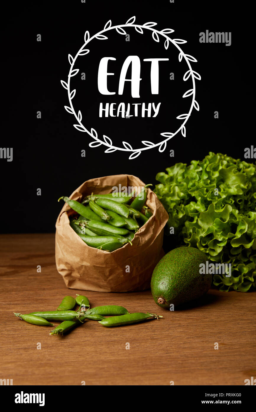close-up shot of avocado, green peas and lettuce on wooden surface with 'eat healthy' lettering - Stock Image