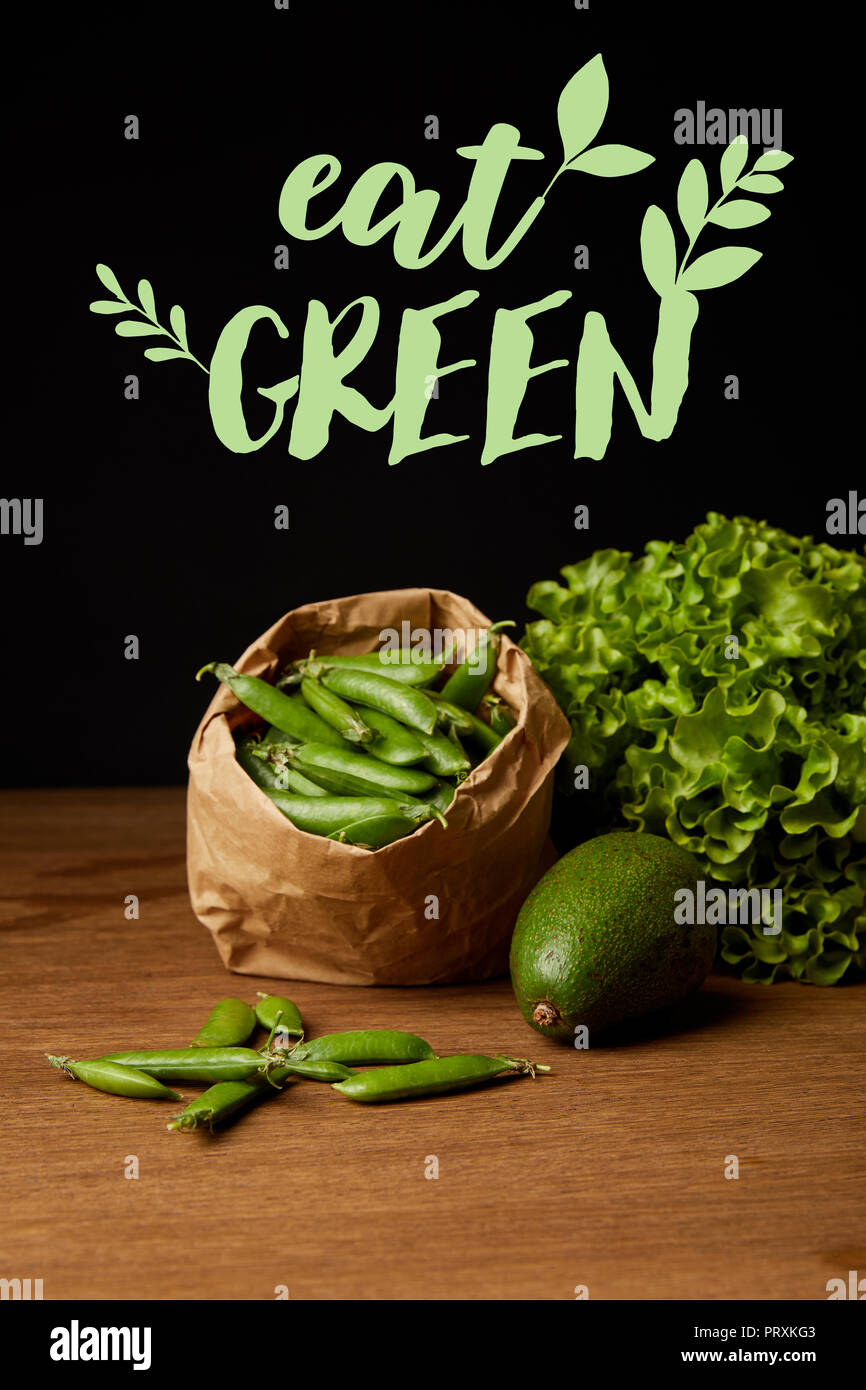 close-up shot of avocado, green peas and lettuce on wooden surface with 'eat green' lettering - Stock Image