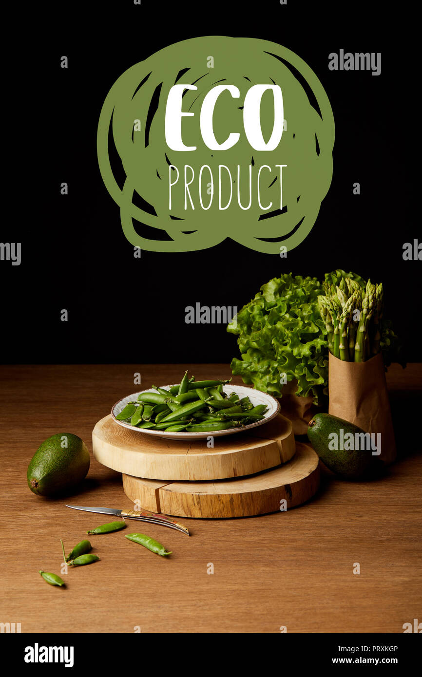 ripe green vegetables on wooden table top with 'eco product' lettering - Stock Image