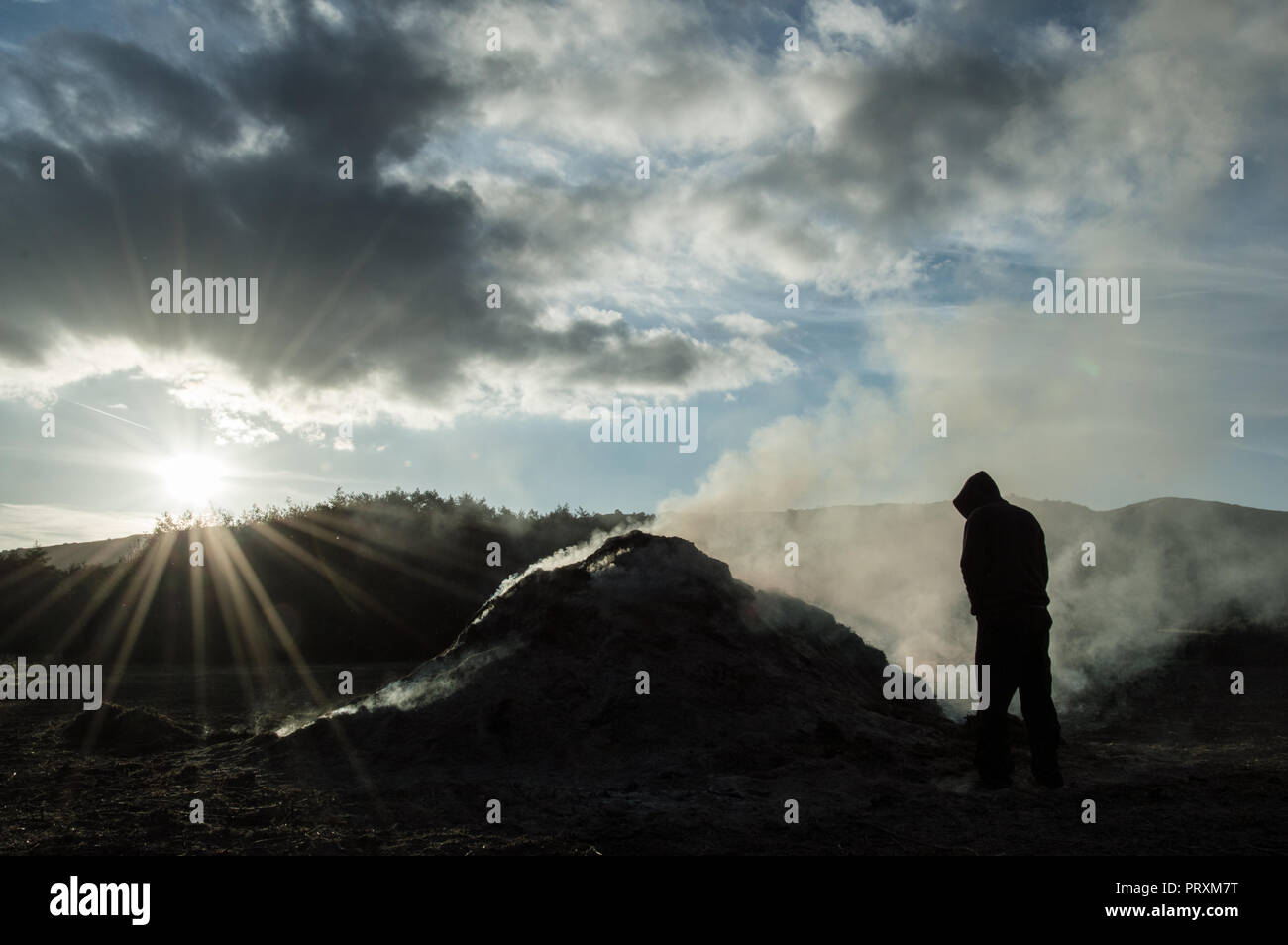 A hooded figure, silhouetted against the white smoke of a bonfire. Backlit from the afternoon sun. - Stock Image