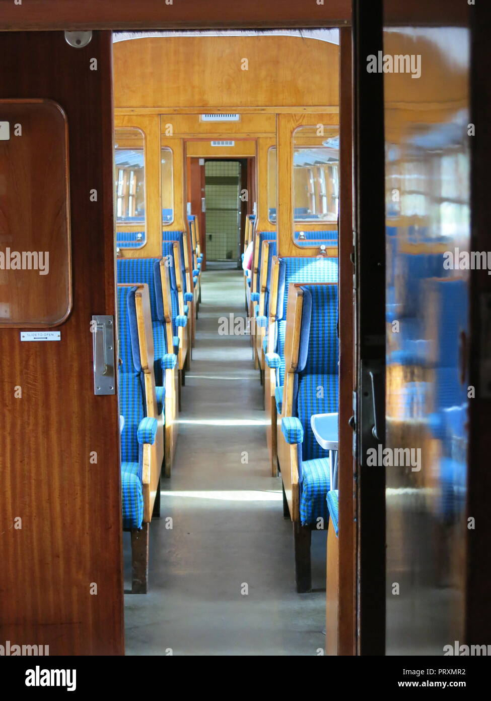 View of blue-upholstered seats in the interior of one of the compartments on a steam train operating on the Gloucestershire Warwickshire Steam Railway - Stock Image
