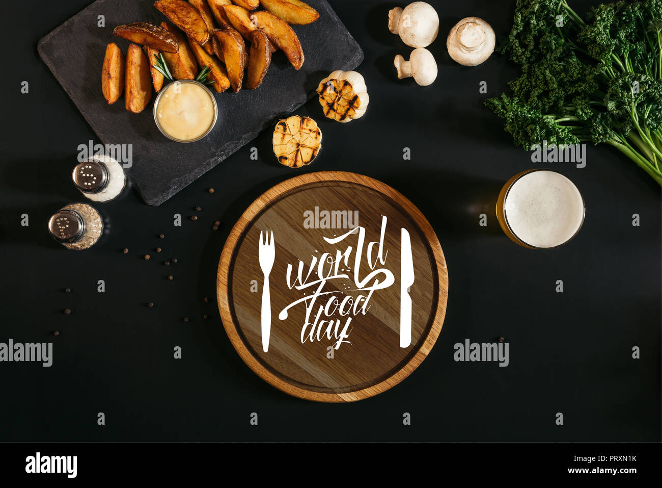 wooden board  with 'world food day' lettering with fork and knife, glass of beer and baked potatoes with sauce and spices on black - Stock Image
