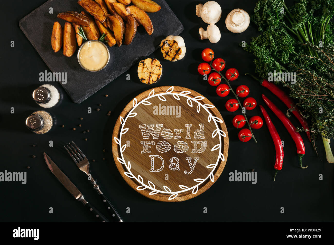 top view of wooden board with 'world food day' lettering, vegetables and baked potatoes on black - Stock Image