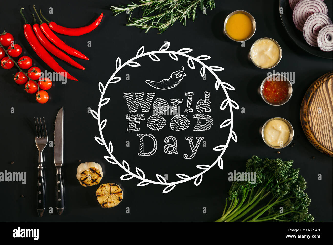 top view of various sauces, grilled garlic, fork with knife and fresh vegetables with herbs on black background with 'world food day' lettering - Stock Image