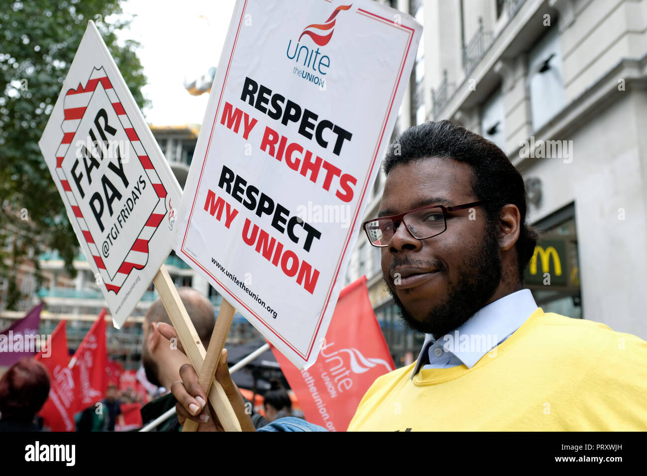 A man seen standing next to a poster saying Respect my rights, respect my Union and Fair pay during the protest. Wetherspoons, TGI Fridays, and McDonald's workers rally together in London to demand better working conditions and a fair pay in the hospitality industry. - Stock Image