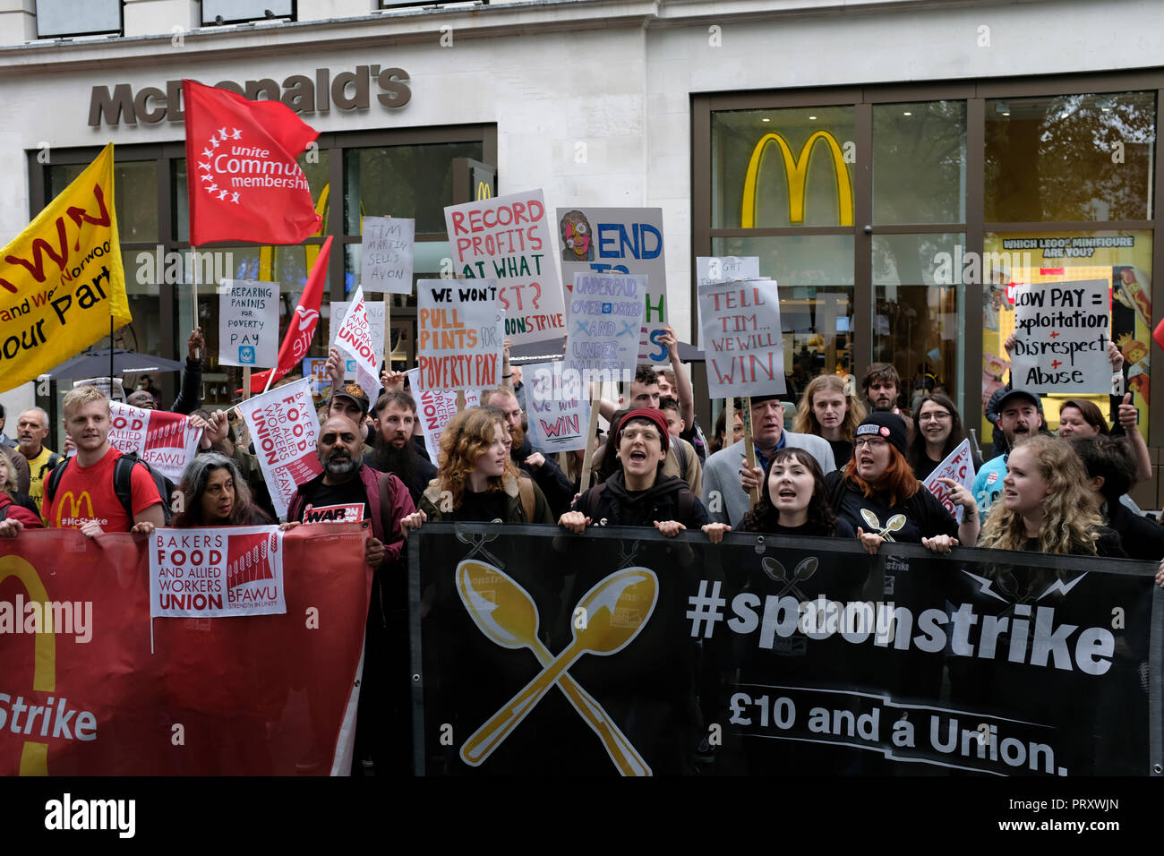 Protesters seen holding banners and flags outside Mc Donalds during the protest. Wetherspoons, TGI Fridays, and McDonald's workers rally together in London to demand better working conditions and a fair pay in the hospitality industry. - Stock Image