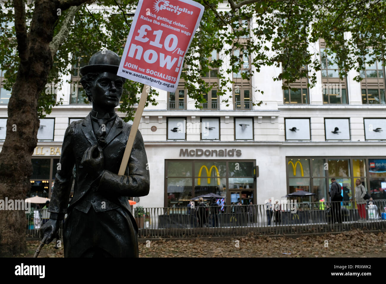 A Charles Chaplin sculpture seen holding a poster saying £10/hr Now! during the protest. Wetherspoons, TGI Fridays, and McDonald's workers rally together in London to demand better working conditions and a fair pay in the hospitality industry. - Stock Image
