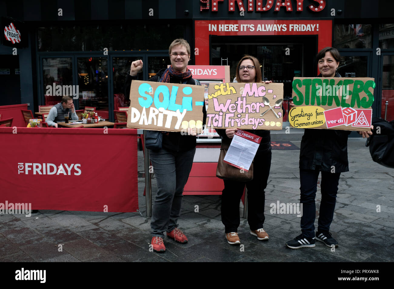 Protesters seen holding posters in front of a TGI Fridays during the protest. Wetherspoons, TGI Fridays, and McDonald's workers rally together in London to demand better working conditions and a fair pay in the hospitality industry. - Stock Image
