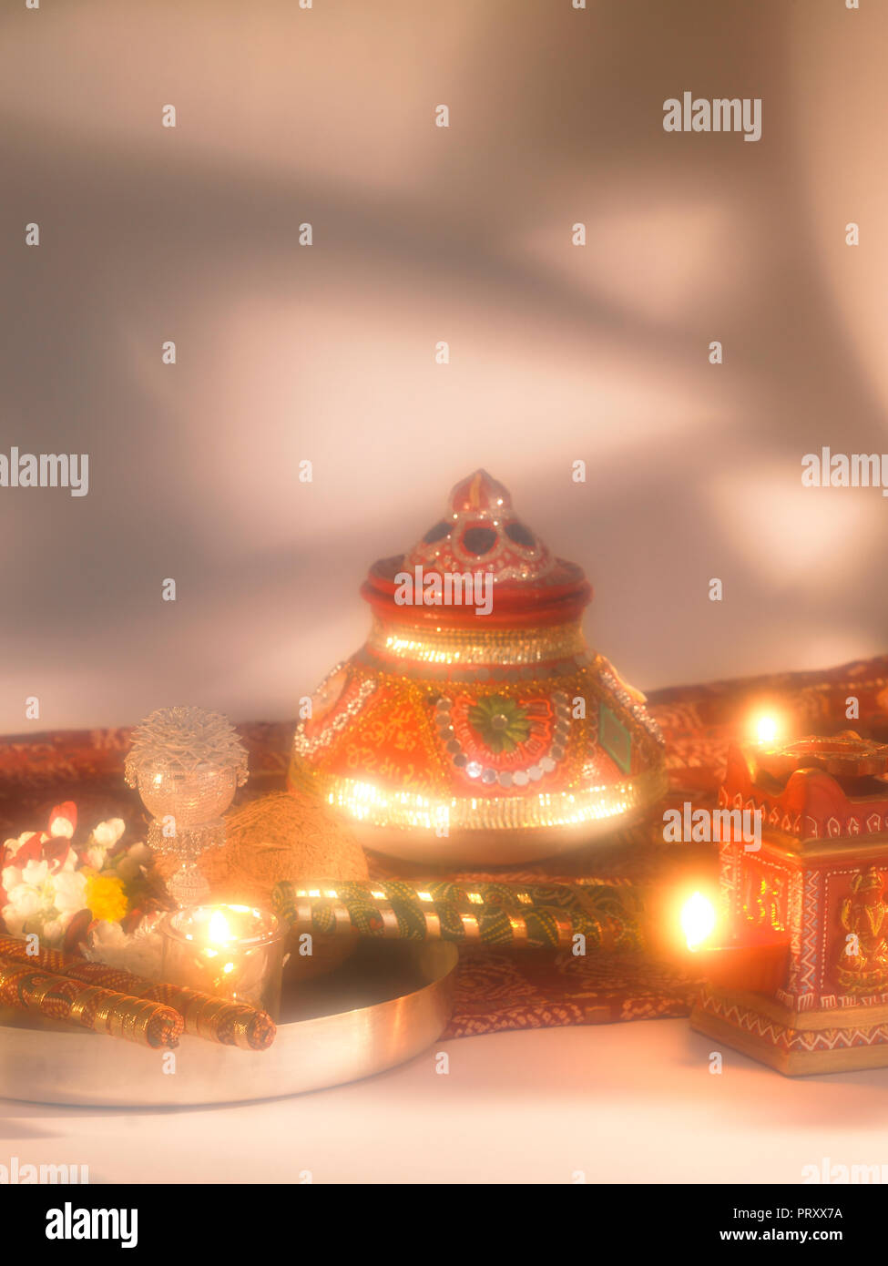 A STILL LIFE OF DASSERA FESTIVAL OBJECTS IN MUMBAI INDIA SHOWING A KALASH/POT, DIYAS, SWEETS, BANDHANI, SAREE, SILVER THALI WITH COCONUT, DIYA, FLOWER Stock Photo