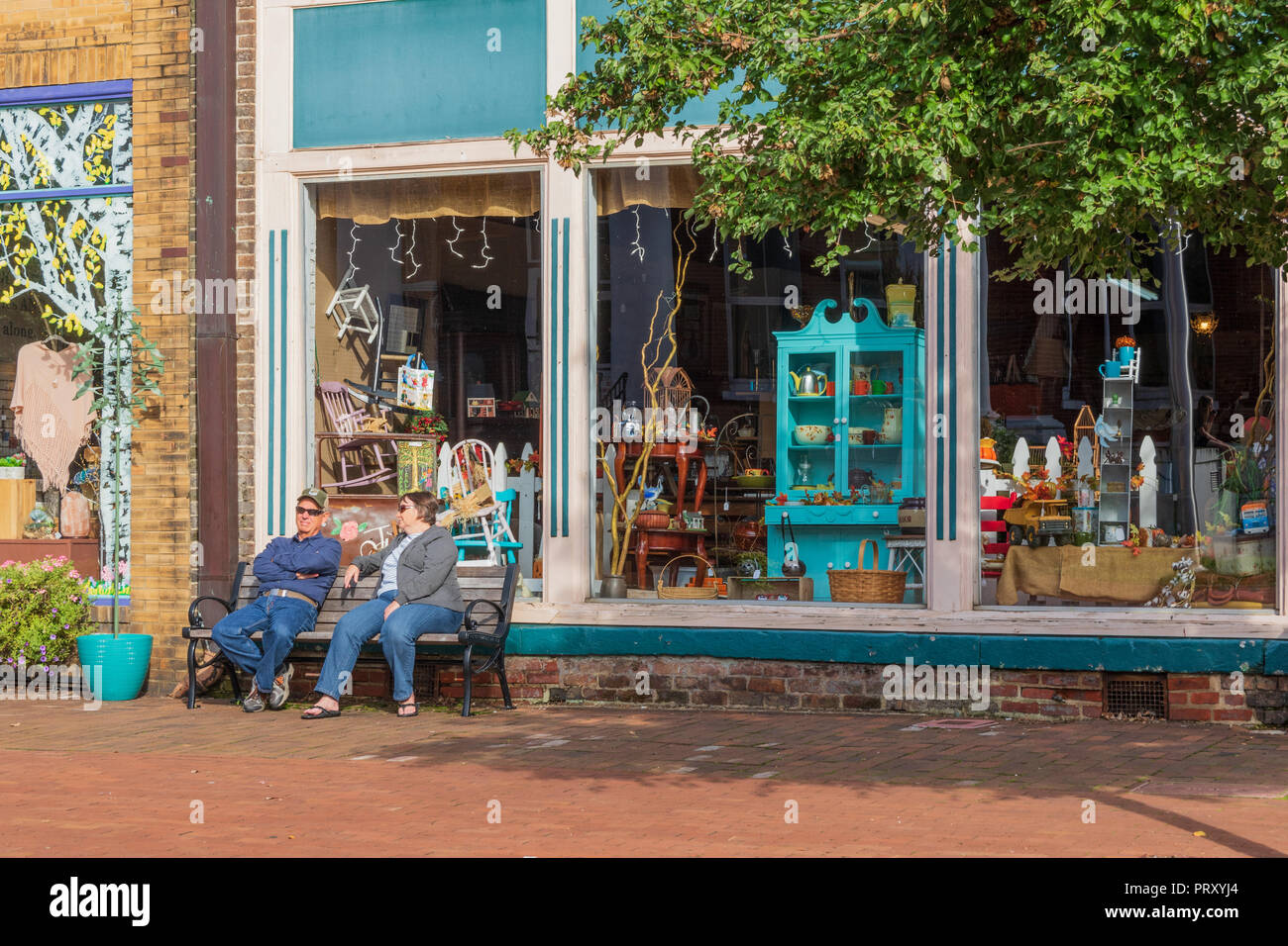 JONESBOROUGH, TN, USA-9/29/18: A man and woman rest and talk on a  bench in historic Jonesborough, in front of colorful stores. Stock Photo