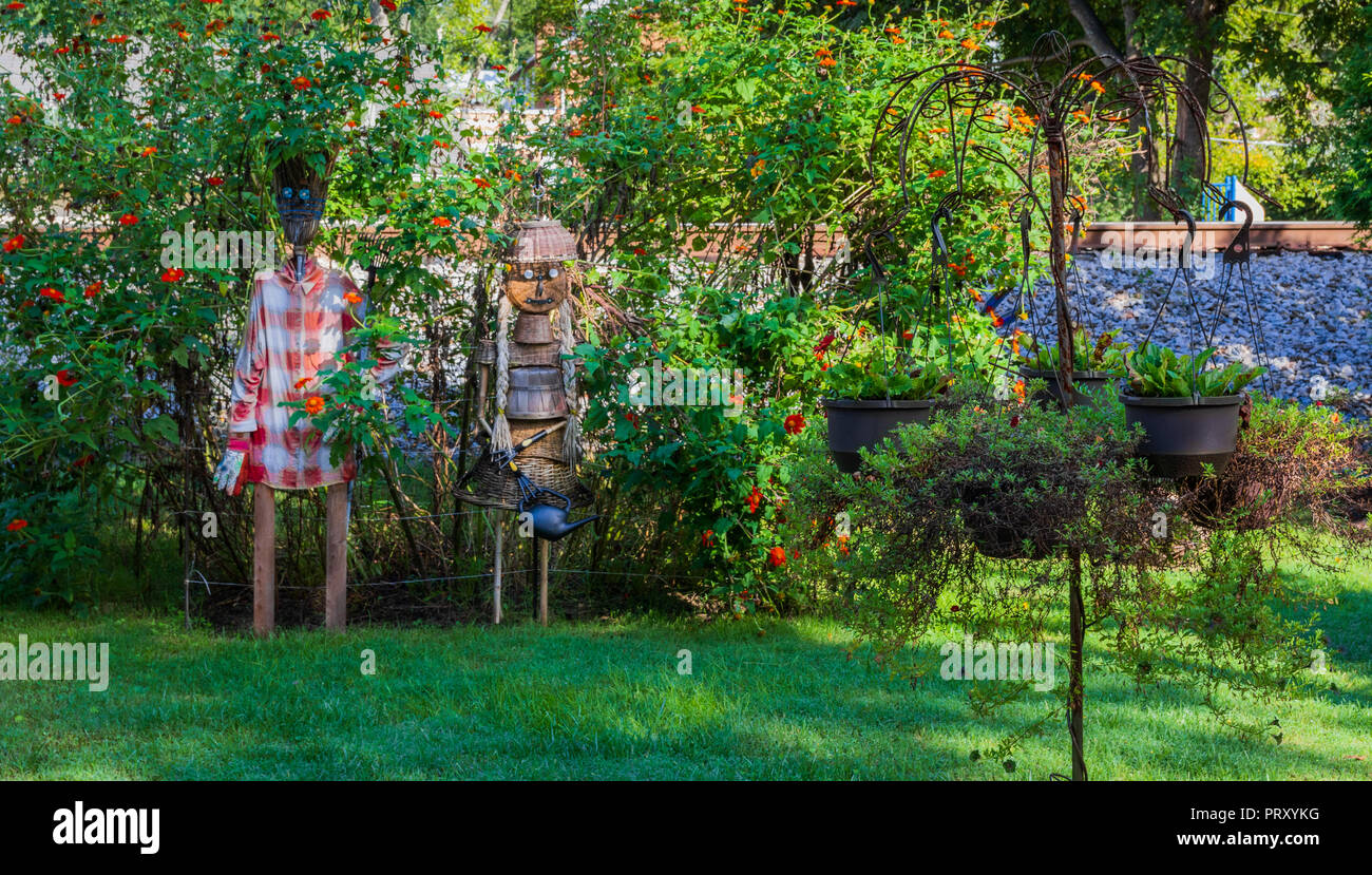 JONESBOROUGH, TN, USA-9/29/18: Two scarecrows, depicting homeowner gardeners, made from baskets and wood sticks stand in a flower-filled yard. Stock Photo