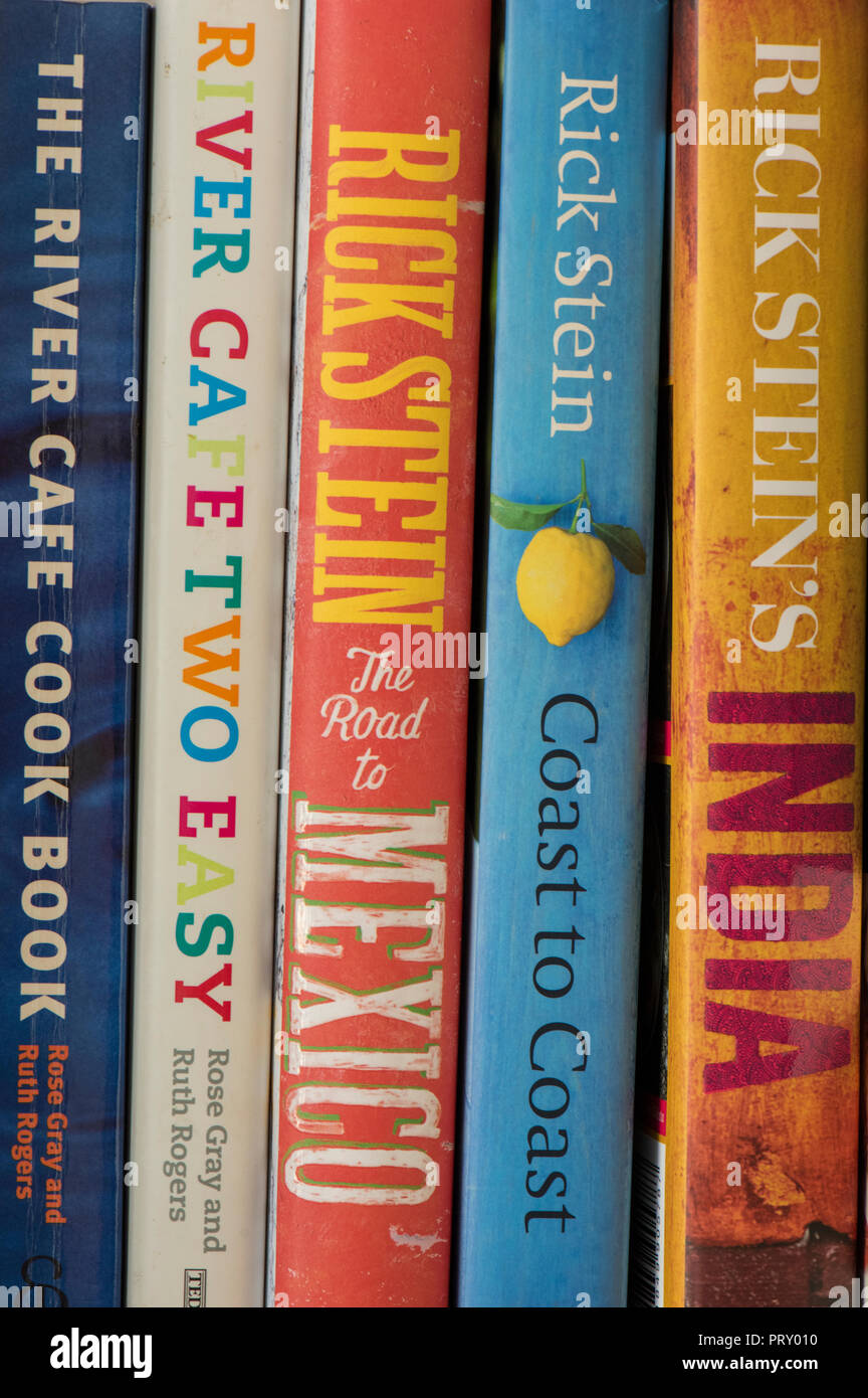 a selection of colourful cookery books on a shelf including those by rick stein and hugh fearnley whittingstall. - Stock Image