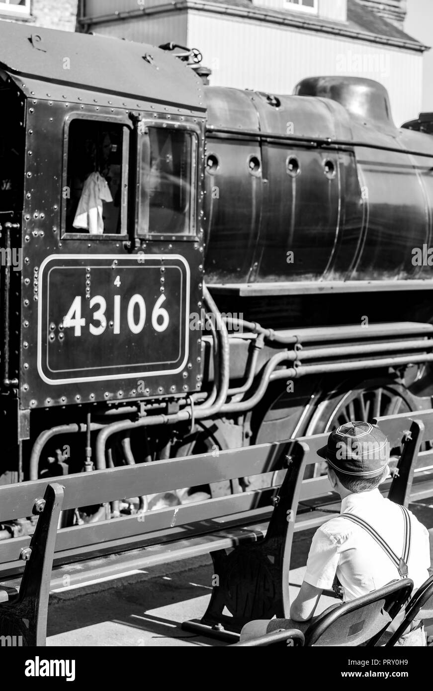 Black & white rear view, wartime 1940's school boy in cap & braces, sitting on platform watching vintage steam trains dreaming of being engine driver. - Stock Image