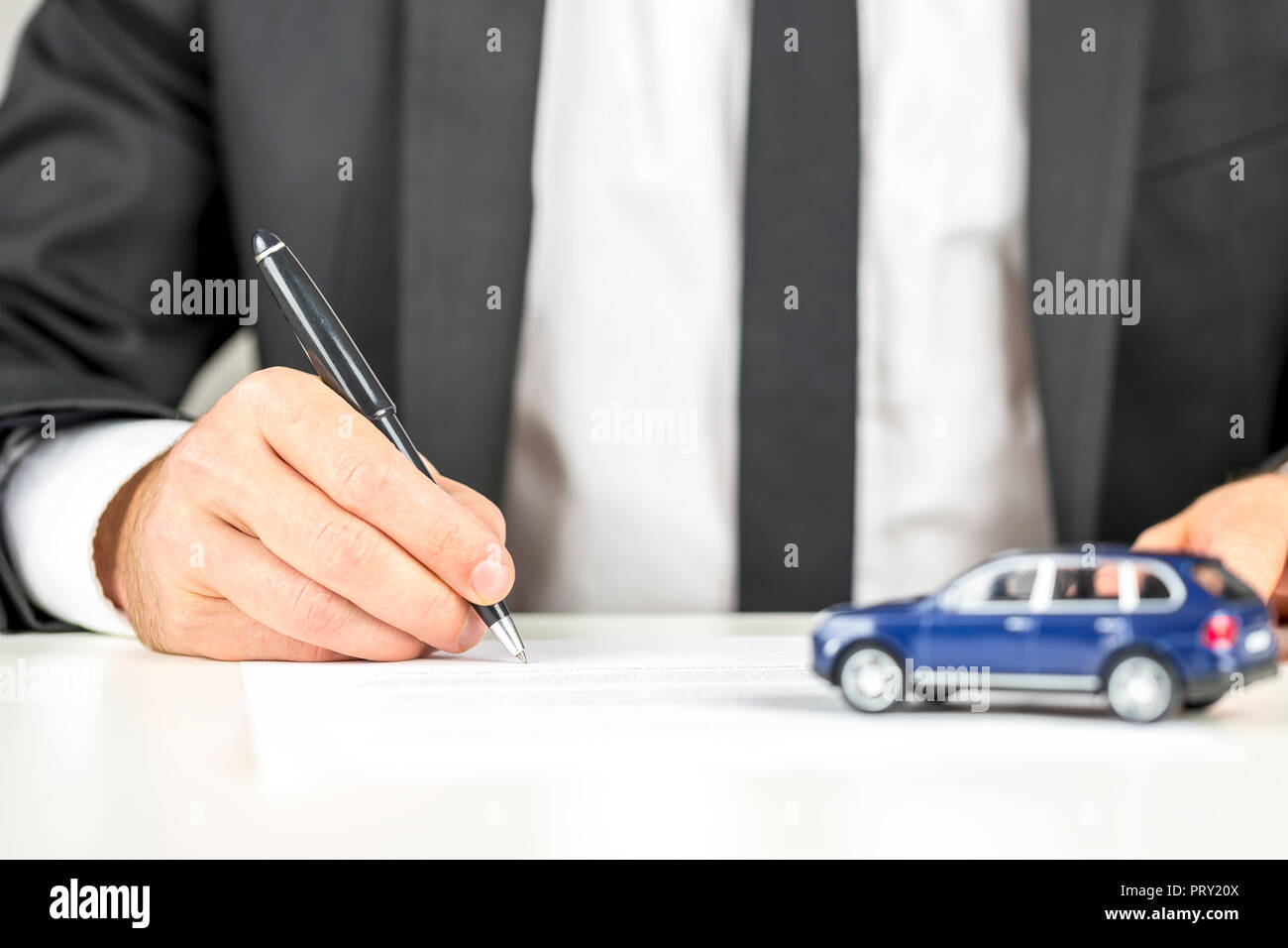 closeup of man signing a contract of car sale stock photo 221255802