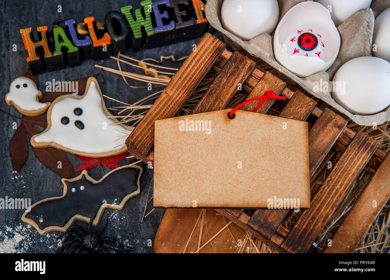 funny halloween treats, eyeball in egg on dark background, copy