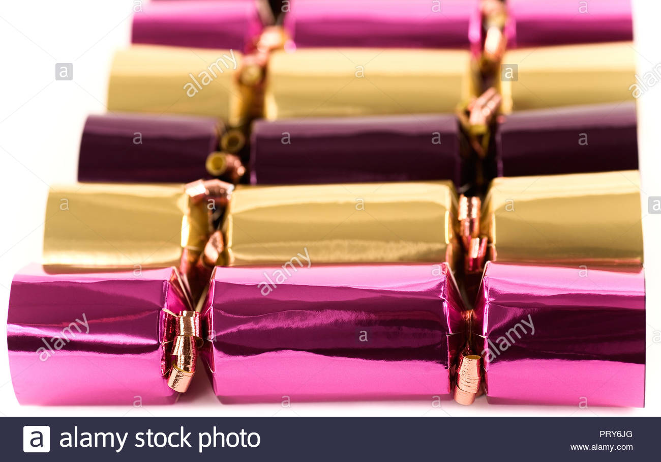 christmas or new years eve party crackers in a row against white background