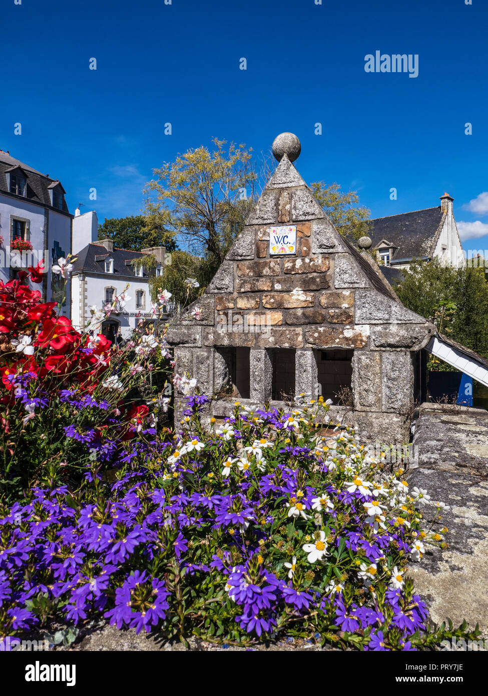 Historic quirky notable small stone WC lavatory toilet building on the banks of the River Aven in Pont-Aven Brittany France - Stock Image