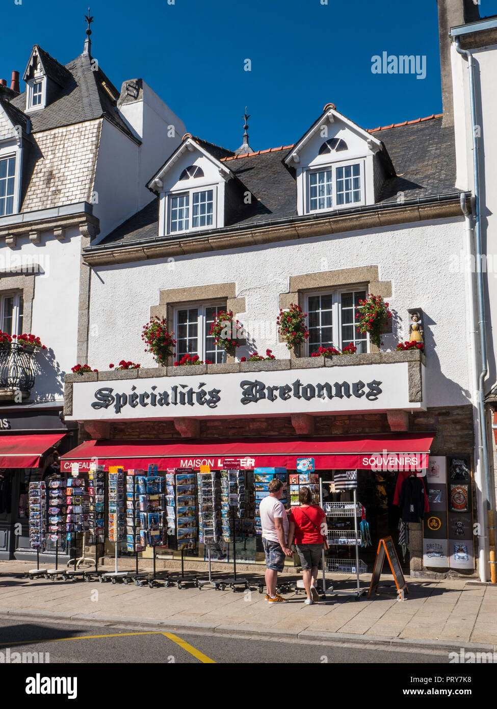 PONT AVEN TOWN BRITTANY FRANCE Pont-Aven village shopping centre with couple browsing holiday vacation postcards Finistère  Southern Brittany France - Stock Image