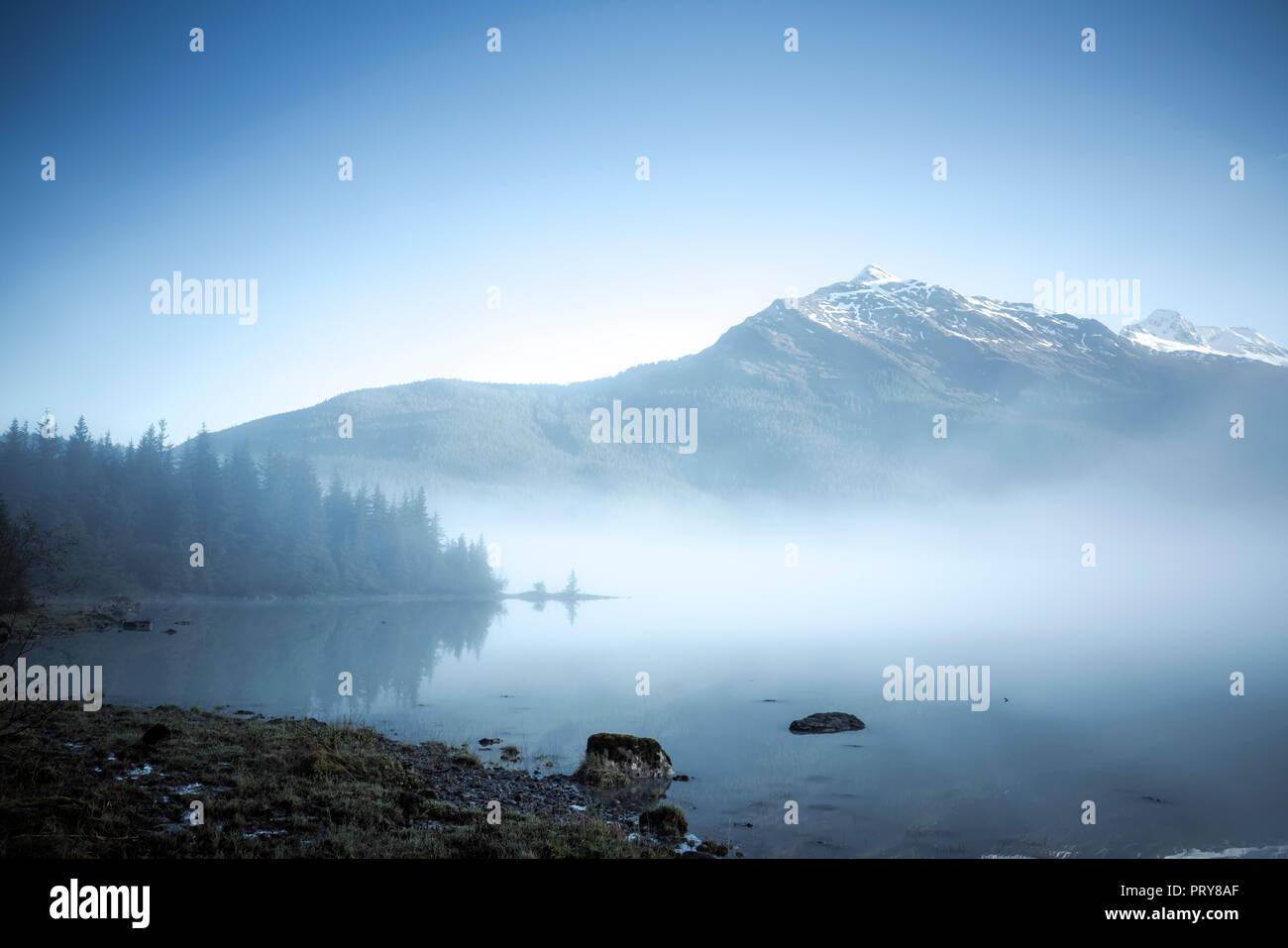Fog lifting on a summer morning at Mendenhall Lake near Juneau. - Stock Image