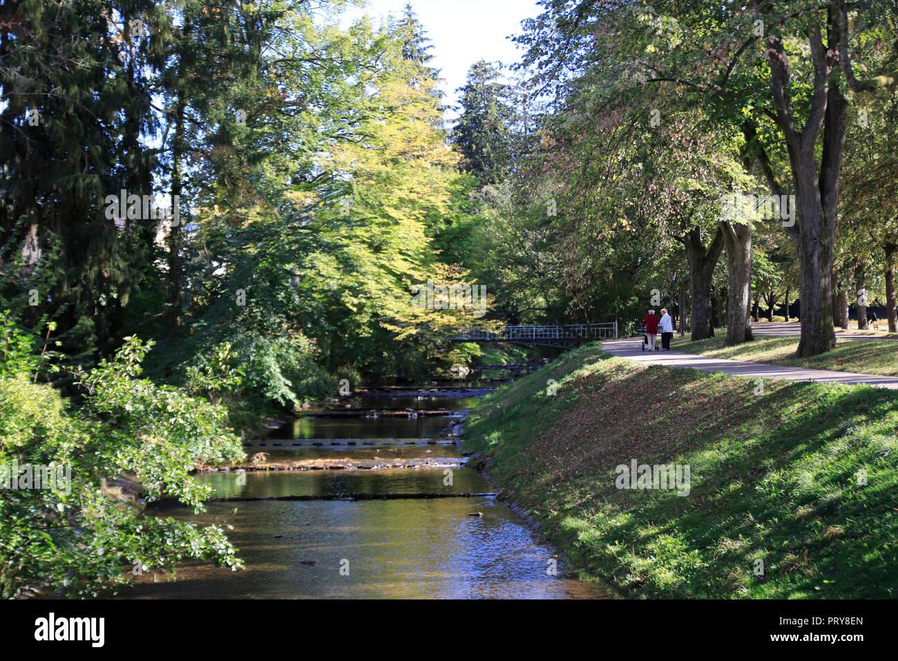 Berühmte Lichtentaler Allee, mit Radweg, Bach Oos und Spaziergänger in Baden-Baden im Herbst - Stock Image