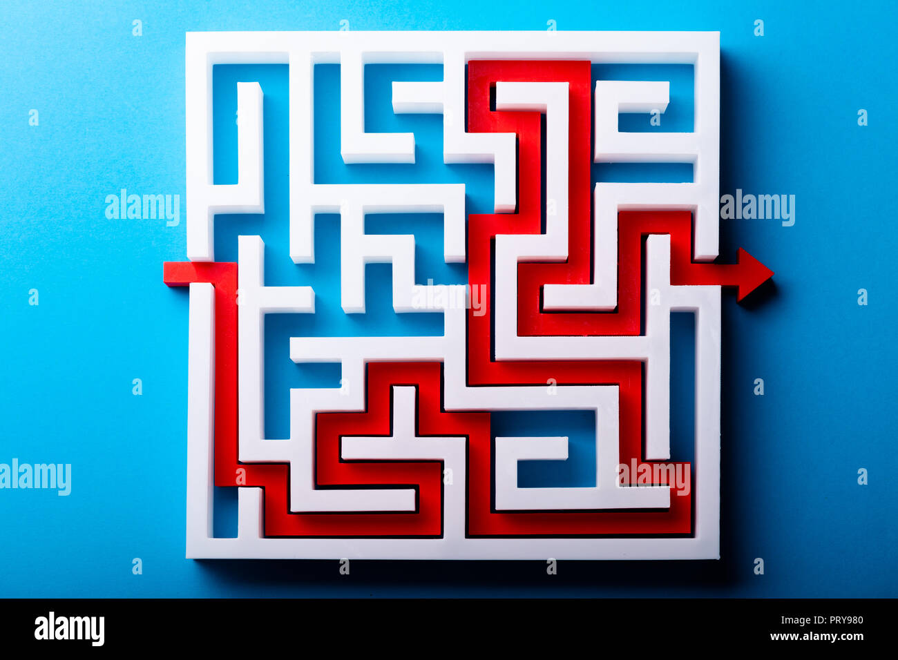 High Angle View Of Red Arrow Showing Path Through Maze On Blue Background - Stock Image