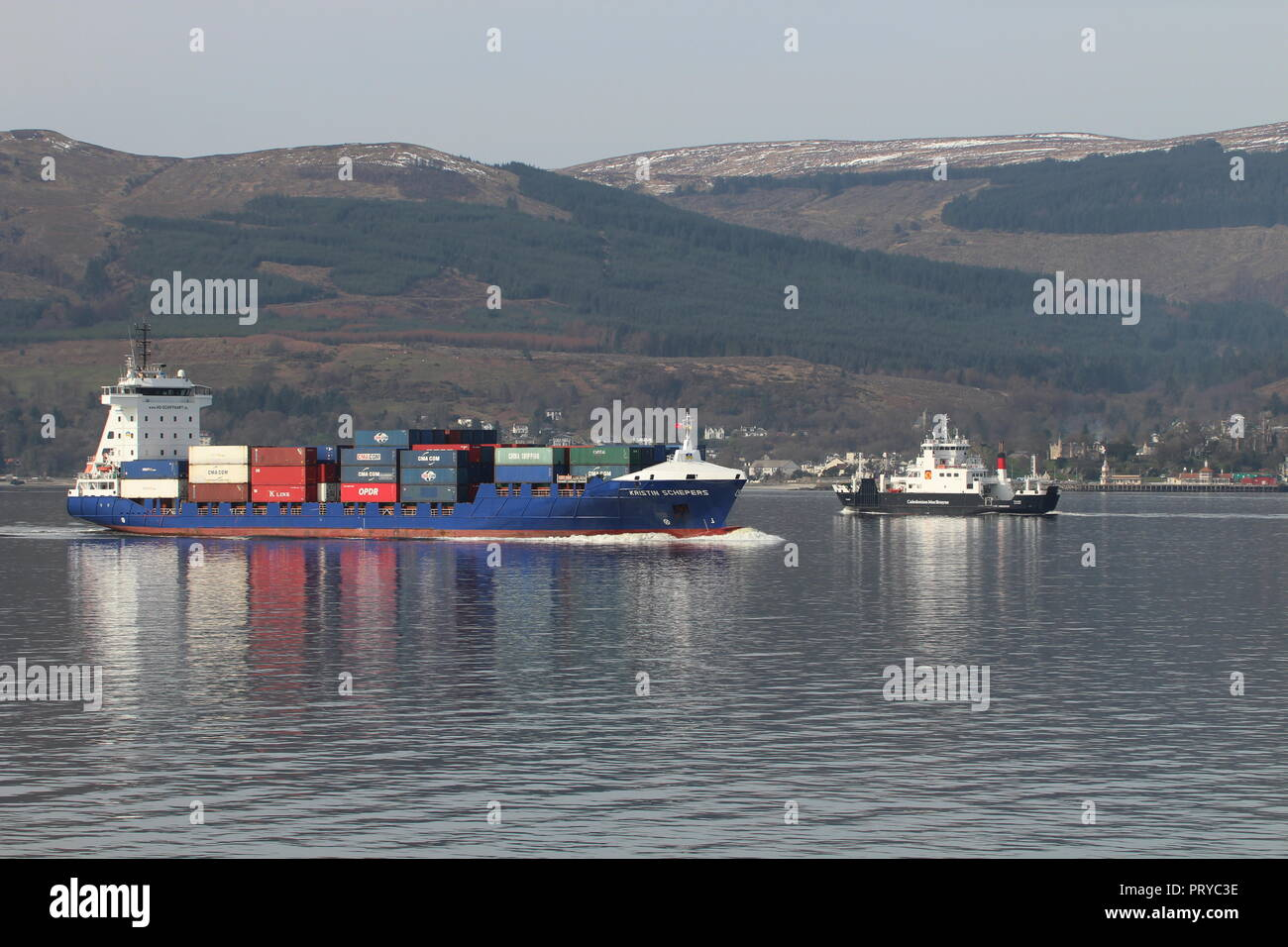 The container ship MS Kristin Schepers heading up the Firth of Clyde, passing the Caledonian MacBrayne car ferry Coruisk on an outbound journey. Stock Photo