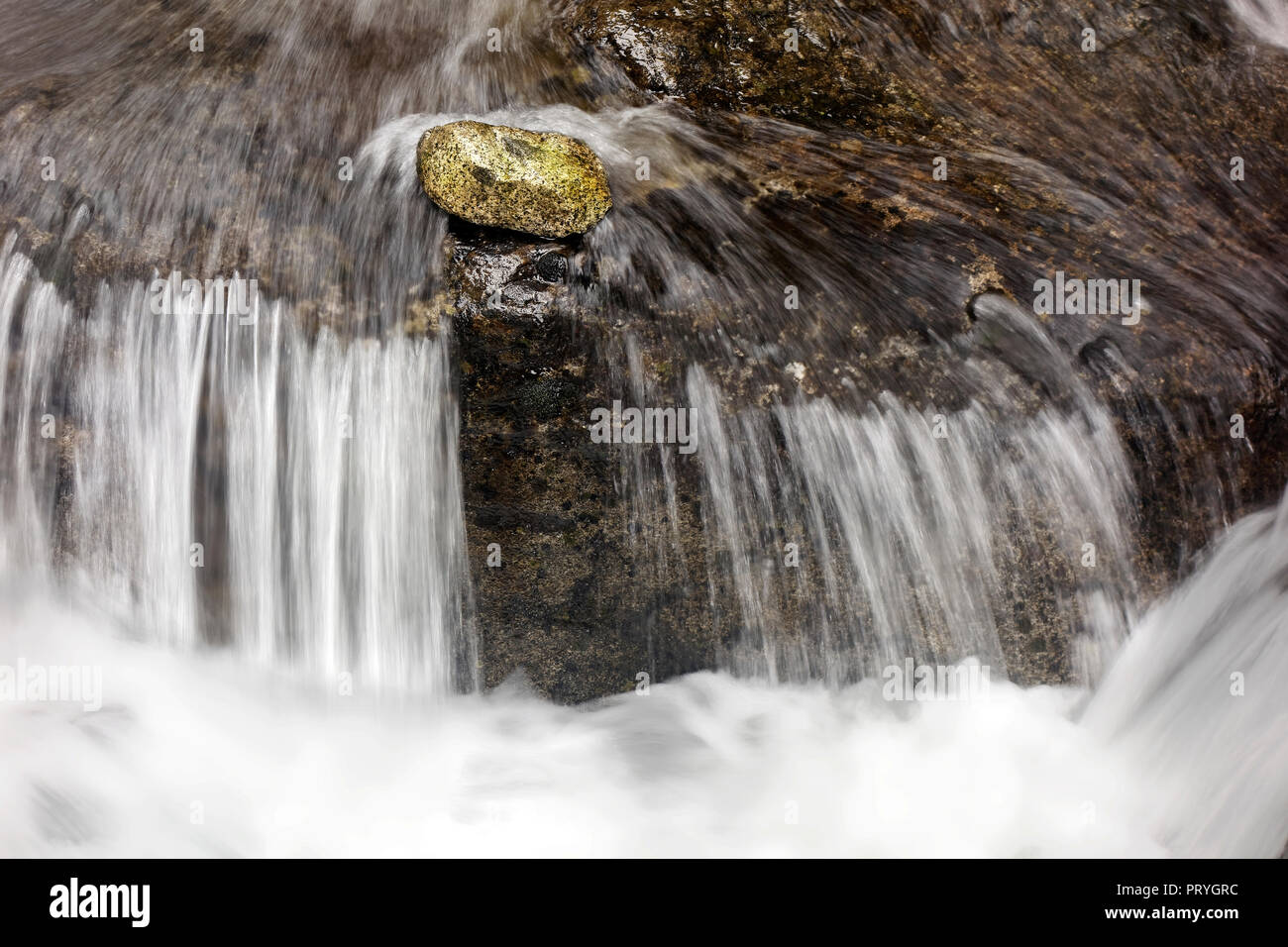 Stone lies in front of a small waterfall in current, mountain stream, symbolism, steadfastness, all against one - Stock Image
