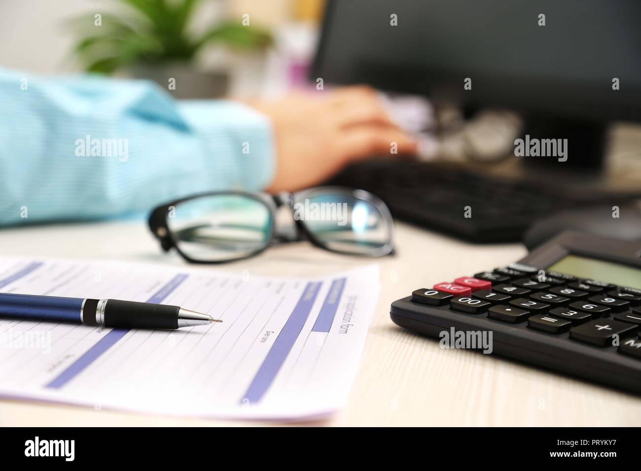 Picture of man is typing on keyboard. Picture of application form, pen, calculator and glasses. Stock Photo