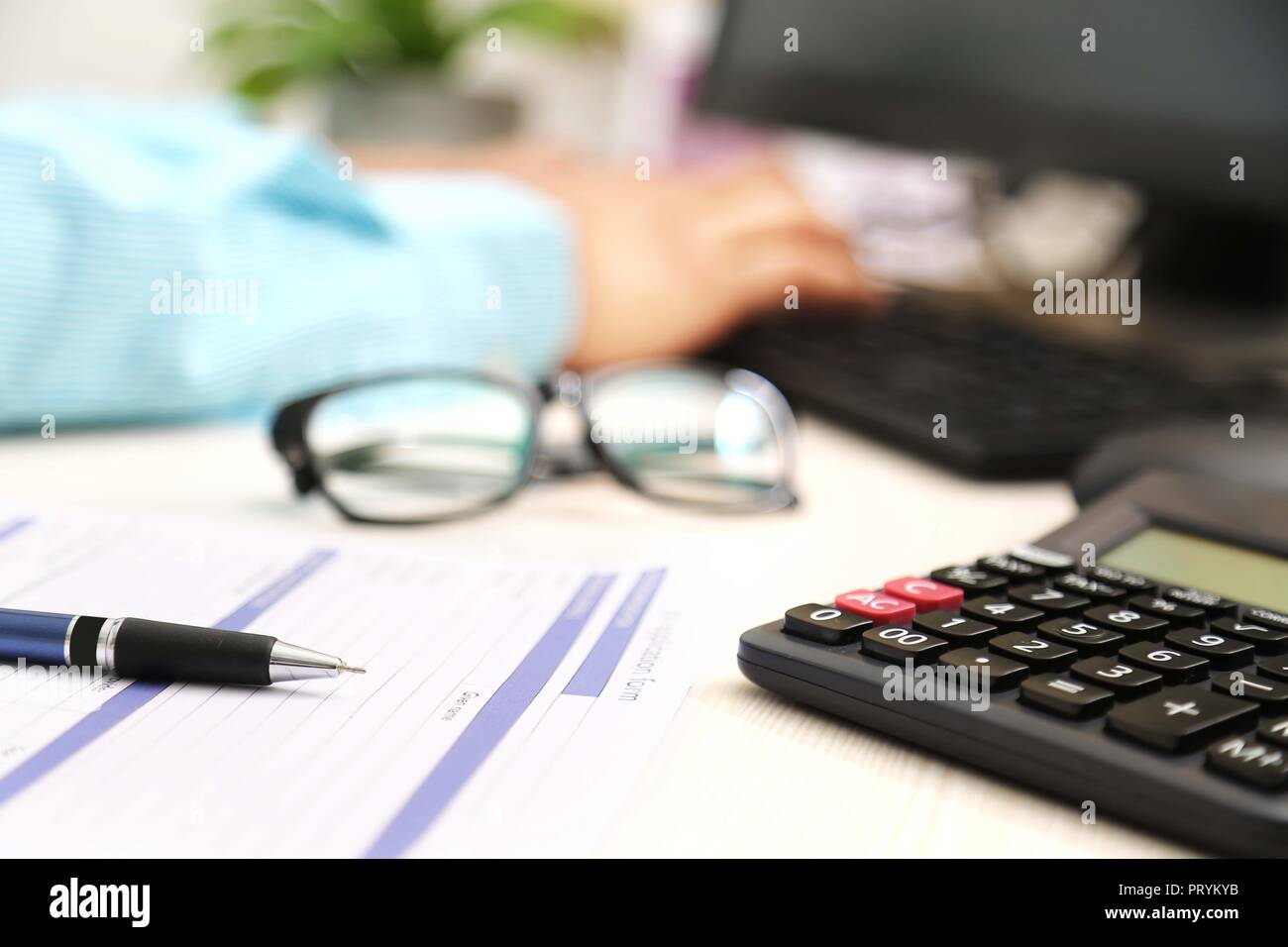 Picture of man hand is typing on keyboard. Picture of application form, pen, calculator and glasses. - Stock Image