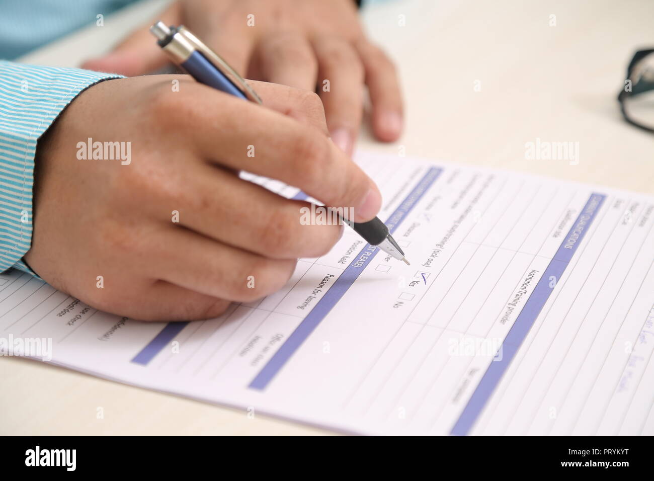 Picture of man holding pen with application form on the table. - Stock Image
