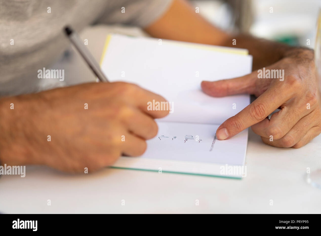 Man signing a book - Stock Image