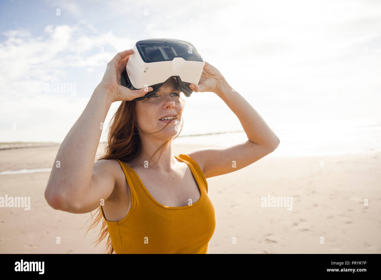Redheaded woman using VR glasses on the beach - Stock Image